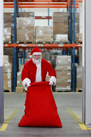 traditional goods: Santa Claus  packing red sack with gifts in storehouse