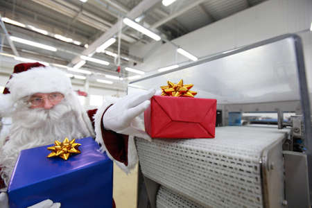 commercialization:  Santa claus receiving gifts from presents machine