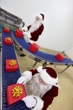 factory line: Two santa clauses working at production line Stock Photo