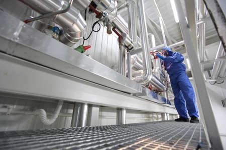 maintenance person: technician in blue uniform controlling technological system