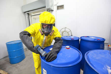 chemical hazard: fully protected in yellow uniform,mask,and gloves professional dealing with chemicals  Stock Photo