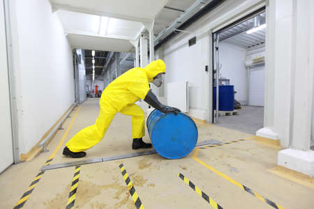 chemical hazard: fully protected in yellow uniform,mask,and rubber gloves and boots worker,rolling the barrel with toxic substance