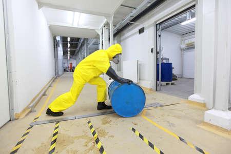riesgo quimico: totalmente protegida con el uniforme amarillo, máscara y guantes de goma y botas de trabajo, haciendo rodar el barril con sustancia tóxica