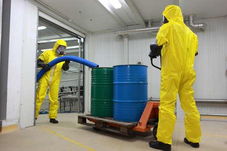 riesgo quimico: Dos especialistas en uniformes de protección, máscaras, guantes y botas de trabajo con los barriles de desechos tóxicos en la fábrica de