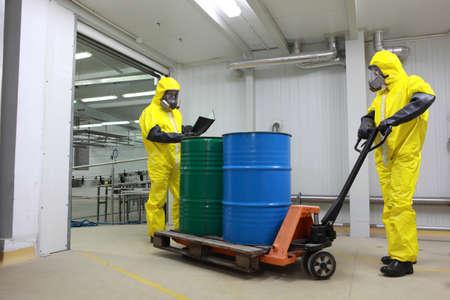 especialistas: Dos especialistas en uniformes de protecci�n, m�scaras, guantes y botas de barriles de transporte de productos qu�micos en la carretilla elevadora en una f�brica Foto de archivo