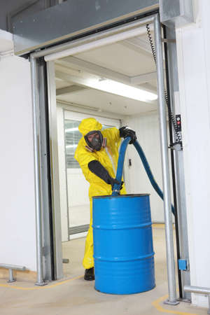 fully protected in yellow uniform,mask,and gloves professional filling large blue barrel with chemicals  photo