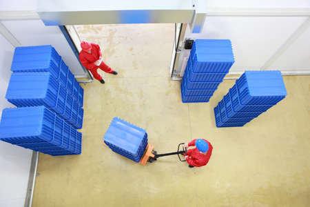 two workers preparing goods delivery in a small company warehouse - overhead view  photo