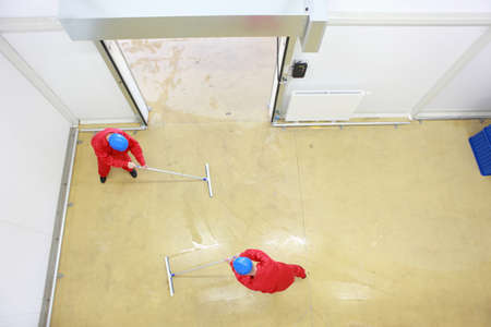 Overhead view of two workers in red uniforms and blue hardhats cleaning floor in industrial building photo