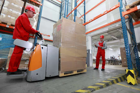 warehousing: Goods delivery - two workers working in storehouse with forklift loader