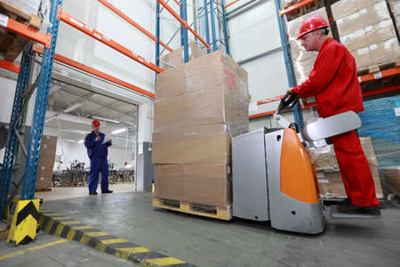 factory worker: Goods delivery - two workers with forklift loader working in storehouse