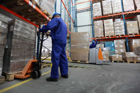 factory worker: Two workers in uniforms and safety helmets working in storehouse  Stock Photo