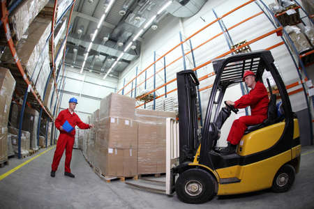 forklift truck: goods delivery in storehouse, two workers reloading pallets with forklift truck