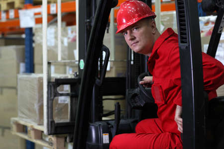 good guys: forklift driver worker in red uniform and safety helmet in storehouse portrait