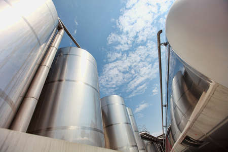silos: Silver silos and tank - industrial infrastructure in wide lens Stock Photo