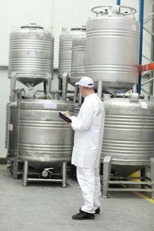 industria alimentaria: De los trabajadores en las poblaciones de blancos uniformes de control de almac�n de alimentos l�quidos