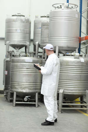food production: Worker in white uniform checking stocks in liquid foodstuff storehouse
