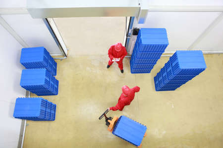 plastic box: goods delivery in storehouse - overhead view of two workers working in small warehouse