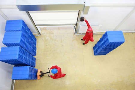 Overhead view of two workers. one is opening a gate another is loading plastic boxes in small warehouse Stock Photo