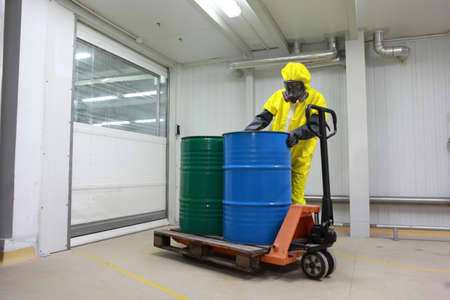 Worker in protective uniform,mask,gloves and boots working with barrels of chemicals on forklift  photo