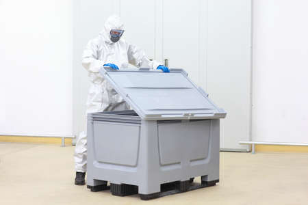 fully protected technician lifting cover of plastic container checking contents  photo
