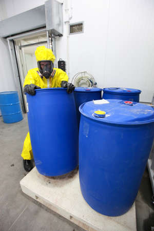 hazardous: Fully protected in yellow uniform, mask, and gloves professional dealing with barrels with toxic substance Stock Photo
