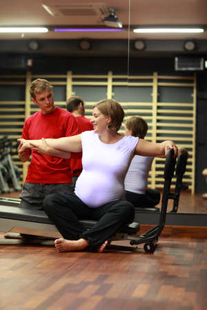 phisical: Phisical therapist stretching happy,pregnant womans arm in gym
