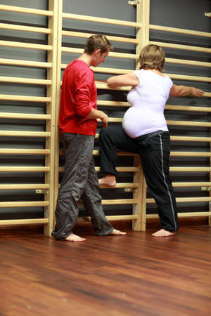Caucasian pregnant woman exercising with child birth instructor   at gym ladder in class labor studio photo