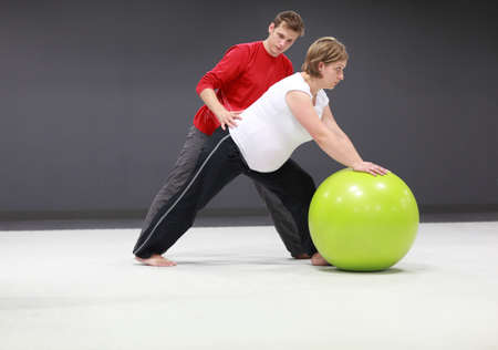 Serious caucasian pregnant woman exercising with personal trainer on large  stability ball in studio photo