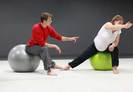 therapist: Serious caucasian pregnant woman exercising with personal trainer on large  stability balls in studio Stock Photo
