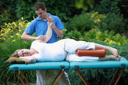 reducing: Physical therapist massaging pregnant woman s arm - reducing stress