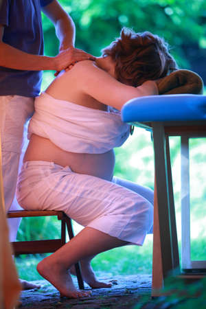 Physical therapist massaging pregnant woman s neck - reducing stress photo