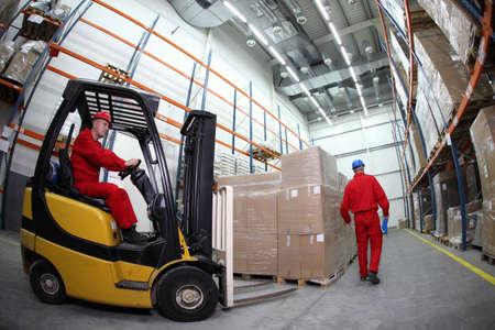 carretillas almacen: dos trabajadores en uniformes rojos y cascos de seguridad en el trabajo en el almacén - lente ojo de pez