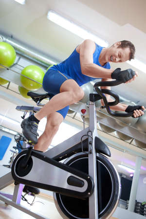 spinning wheel: Cycling fit man on spinning bike in gym