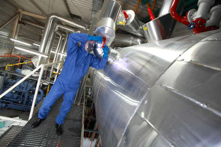 Technician  in mask,gloves,goggles and blue uniform reparing technological system
