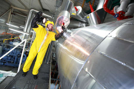 research facilities: Technician with torch in mask,gloves,goggles and yellow uniform controlling technological system