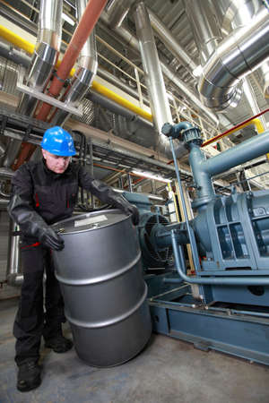 Oil Worker in helmet and uniform, inside refinery dealing with silver oil barrel photo