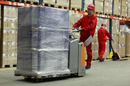 inventario: Dos trabajadores con uniformes y cascos de seguridad de trabajo en el almacén Foto de archivo