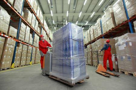 carretillas almacen: Dos trabajadores con uniformes y cascos de seguridad de trabajo en el almacén Foto de archivo