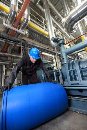 riesgo quimico: Trabajador en la planta de tratamiento con el barril de plástico