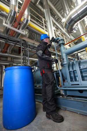 Oil Worker in helmet and uniform, inside refinery checking system