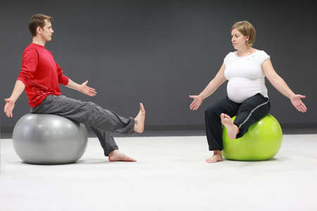 physiotherapist: pregnant woman and personal trainer on large stability balls