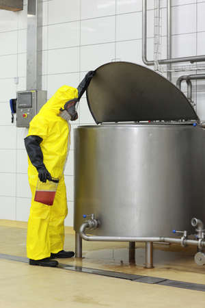 Technician in yellow protective uniform,mask,goggles,gloves  with sample of liquid at large industrial process tank in factory