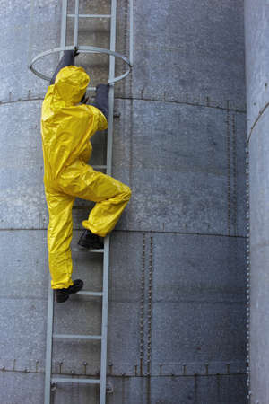 welly: specialist in protective uniform going up a ladder on large industrial  silo in the factory