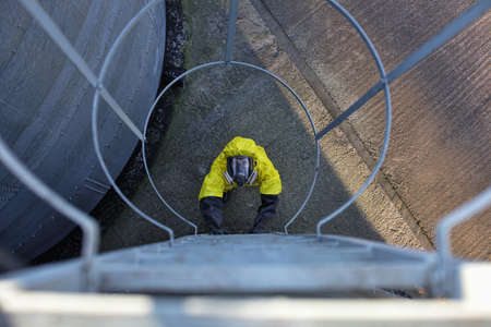 welly: specialist in protective uniform going up a ladder on large industrial  silo