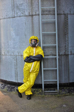 welly: specialist in protective uniform standing at the front of  metal ladder of large industrial  silo Stock Photo