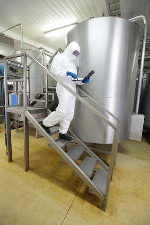 inspector: technician in white uniform focused on tablet, walking down the stairs in industrial process interior Stock Photo