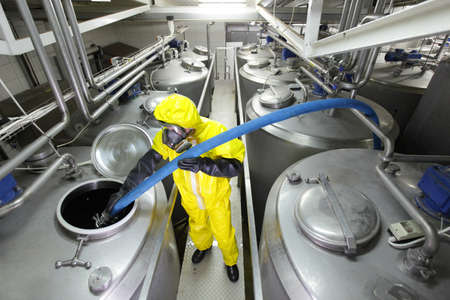 fully protected in yellow uniform,mask,and gloves technician filling large silver tank in plant