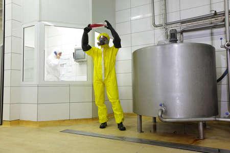 productos quimicos: Dos profesionales de uniforme en el trabajo en plant.one está examinando muestras de líquido en el tanque grande de procesos industriales en la fábrica, otro está llamando en el teléfono Foto de archivo