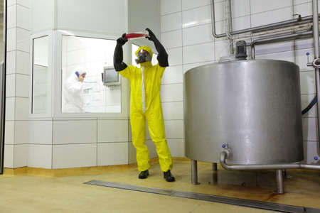 industrial products: Two professionals in uniforms at work in plant.one is examining sample of liquid at large industrial process tank in factory,another is calling on phone Stock Photo