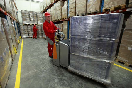 euro pallet: Chain supply - two workers in uniforms and safety helmets working in storehouse Editorial